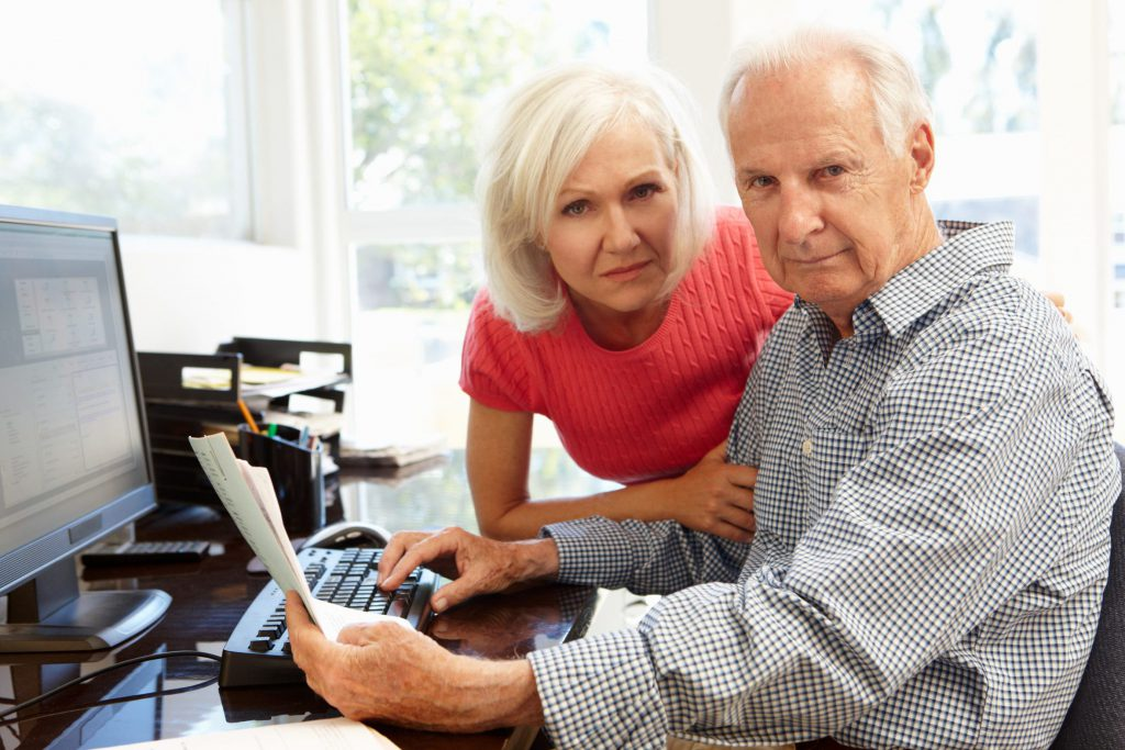 Senior man and woman using computer at home